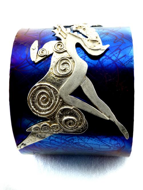 """Βραχιόλι από τιτάνιο και ασήμι. Το φάρδος του είναι 5 εκατοστά και η διάμετρός του 6,5. Ανήκει στην σειρά κοσμημάτων τα οποία έχουν δημιουργηθεί, μετά από σχεδιαστική εξέλιξη,με βάση το """"δαχτυλίδι του Μίνωα"""".  Το """"δαχτυλίδι του Μίνωα"""""""