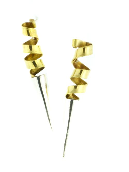 Σκουλαρίκια απο ασήμι 925 και μπρούντζο (μέγιστο μήκος 1.2cm και ύψος 7.5cm). Εφαρμόζουν στο αυτί με καρφάκια από όπου ξεκινάει ελικοειδές έλασμα απο μπρούντζο το οποίο καταλήγει σε ασημένιο κώνο. Το ελικοειδές έλασμα απο μπρούντζο από όπου κρέμονται, επι