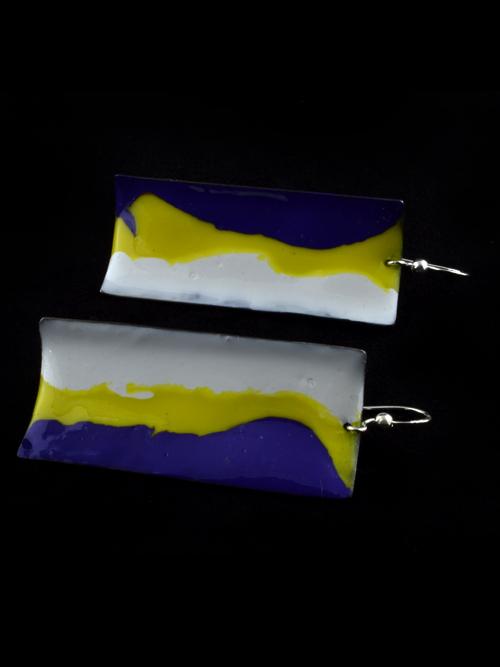 Σκουλαρίκια απο τιτάνιο (γαντζάκι ασημένιο) τα οποία έχουν χρωματική σύνθεση απο ψυχρά σμάλτα. Σε αυτή τη σειρά, το μέταλλο (τιτάνιο) γίνεται κάτι σαν καμβάς για ναΐφ ή γεωμετρικά σχέδια. Πλεονέκτημα το πολύ ελαφρύ τιτάνιο, κατάλληλο για όλες τις ηλικίες